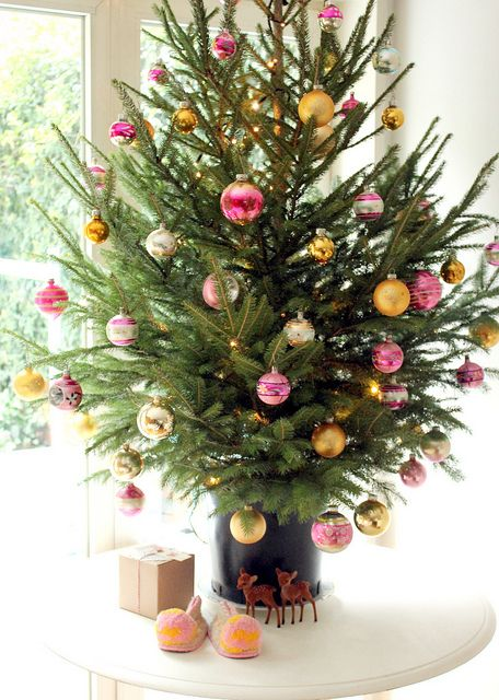 a colorful tabletop Christmas tree decorated with pink and yellow ornaments and nothing else is modern and bold