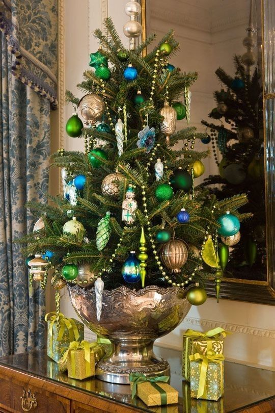 a colorful vintage Christmas tree with bronze, green and blue ornaments, beads and florals and some matching gifts under it
