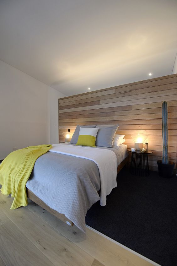 a contemporary bedroom is completed with a light-colored wooden wall and matching floor to make it feel cozy yet totally ethereal