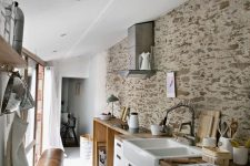 a contemporary kitchen with a painted stone wall and butcherblock countertops that make it feel cozy and look warmer