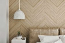 a contemporary light-colored geometric wooden wall echoes with the leather upholstered bed creating a light mood in the space