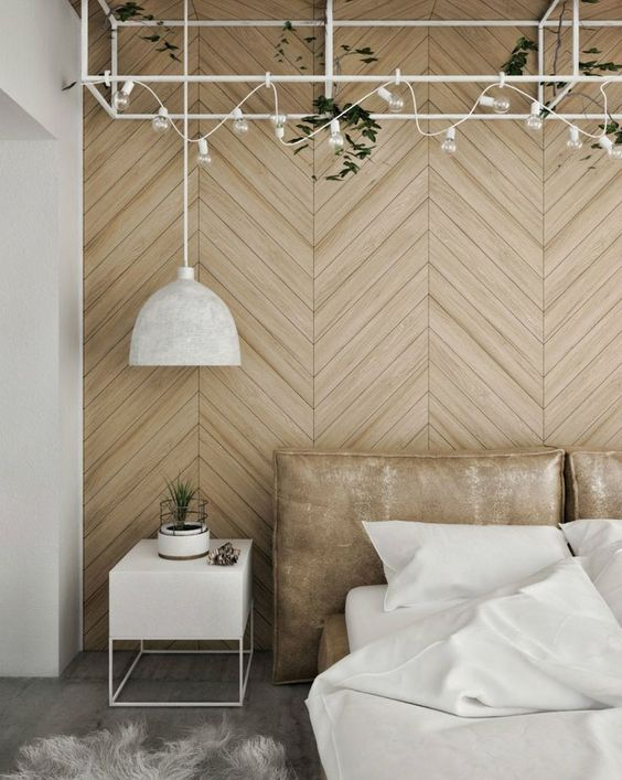 a contemporary light colored geometric wooden wall echoes with the leather upholstered bed creating a light mood in the space