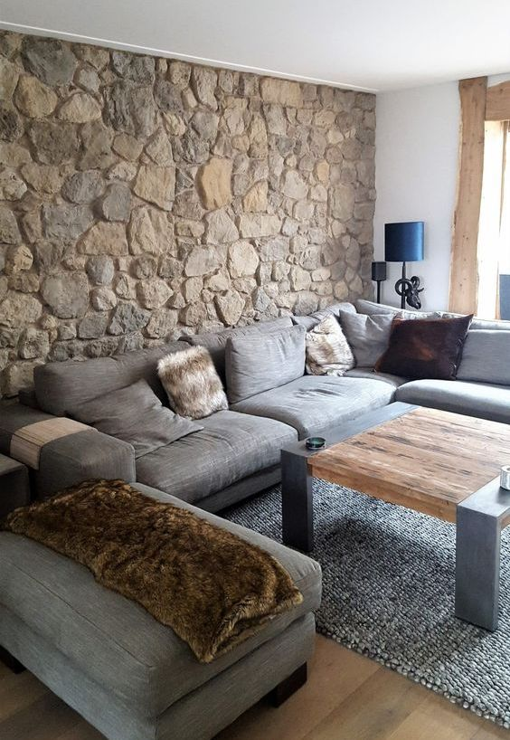 a contemporary living room with a natural stone accent wall and a wooden table that warm up and cozy up this rather cold space