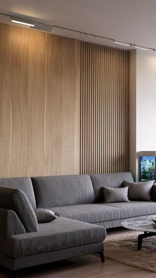 a contemporary living room with a wooden wall done plain and of slats, a grey sectional and a marble table is very refined