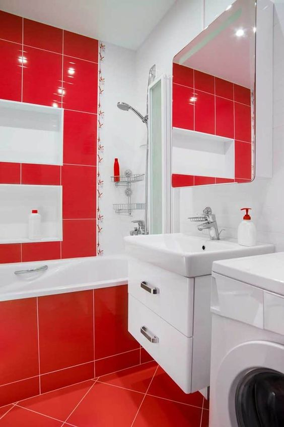 a contemporary red and white bathroom with large scale tiles, white niches, a large mirror and a white vanity with drawers