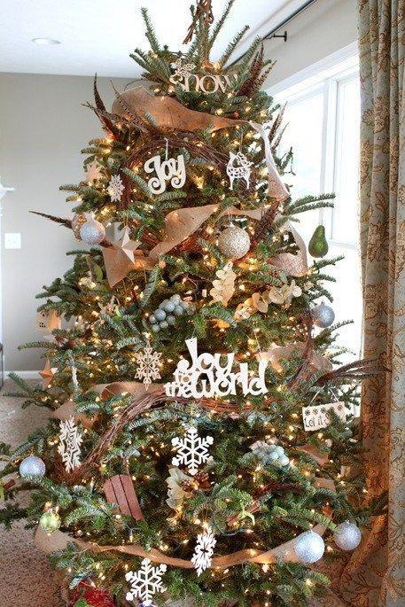 a cool rustic Christmas tree with lights, vine, burlap ribbons, silver ornaments, snowflakes and feathers