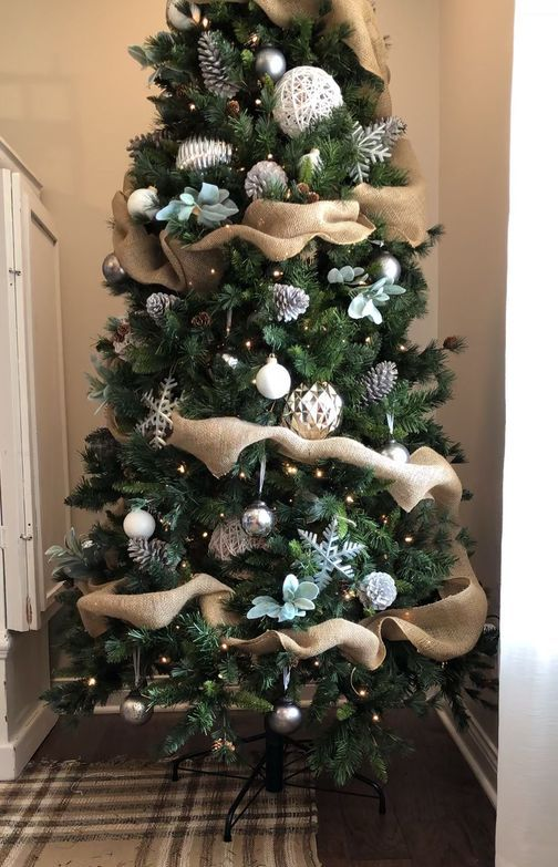 a country Christmas tree with pinecones, pale greenery, snowflakes, metallic ornaments and yarn balls is chic