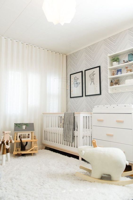 a cozy Scandinavian nursery with a printed wallpaper wall, white furniture, a shelving unit and lots of neutral and simple toys
