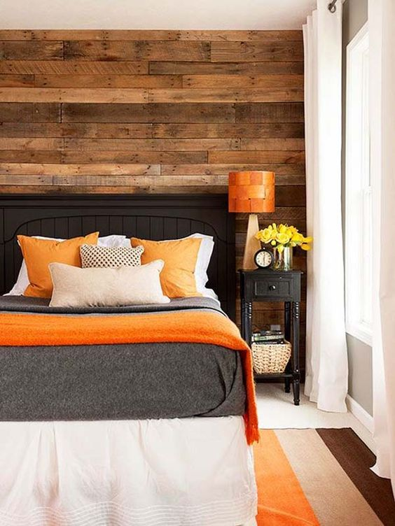 a cozy bedroom with a reclaimed wooden wall and bold orange accents that add a cheerful touch to the space