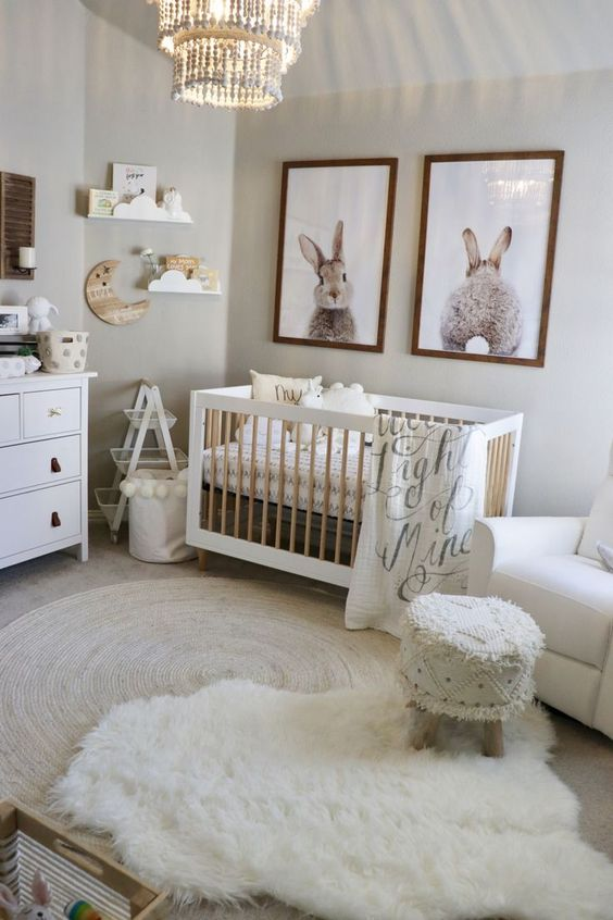 a cozy boho nursery with neutral furniture, layered rugs, an ottoman, a gallery wall with bunnies and some shelves on the wall