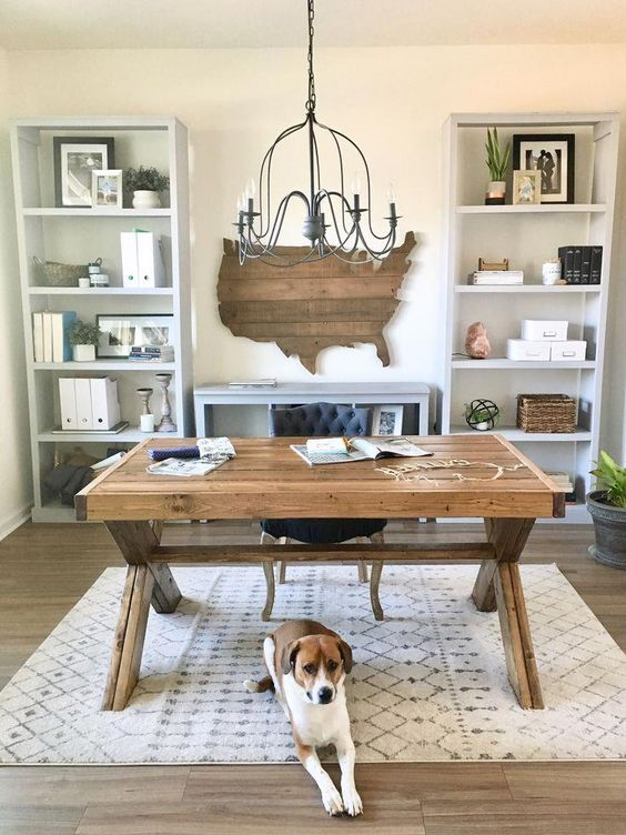 a cozy neutral rustic home office with a wooden trestle desk, a state artwork, a metal chandelier and dove grey storage units