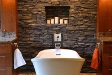 a cozy rustic bathroom with amber wooden cabinets, a faux stone wall with niches for candles and a mosaic pebble floor