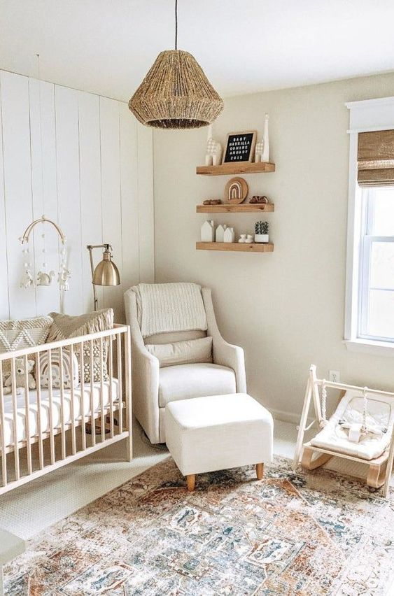a cozy rustic boho nursery in neutrals with neutral wooden and upholstered furniture, wooden shelves, woven shades and a jute pendant lamp