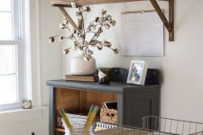 a cozy rustic home office with open shelves, a grey storage unit, a wooden desk and some metal touches and potted plants