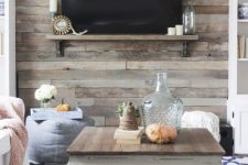 a cozy space with a rustic reclaimed wooden wall and a coffee table that matches, wood adds a rustic feel here