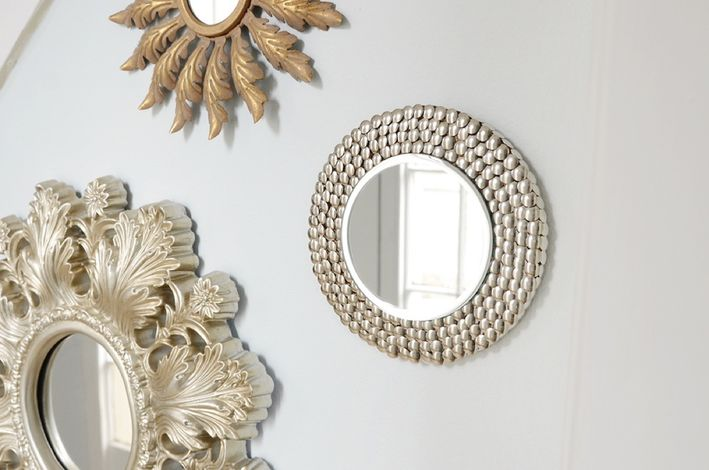 a decorative mirror hack using a small mirror, an IKEA HEAT trivet and some thumbtacks