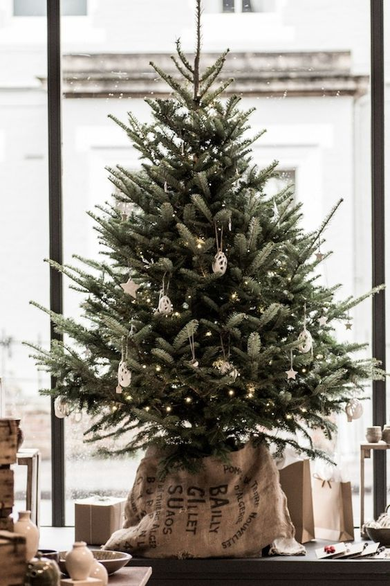 a delicate tabletop Christmas tree decorated with lights, white clay ornaments and put into a sack for a slight industrial feel