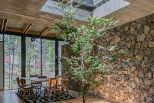 a dining space with a skylight, a tree under it and a stone accent wall to bring naturre inside the house