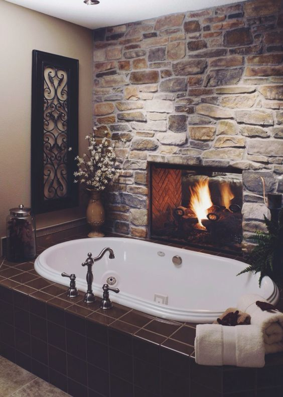 a dramatic bathroom with a faux stone accent wall that features a fireplace, some statement plants and vintage faucets