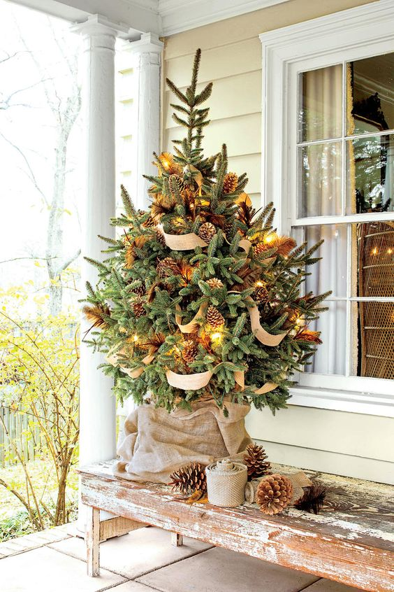 a fantastic rustic tabletop Christmas tree decorated with lights, pinecones and burlap ribbons is easy to repeat in your backyard