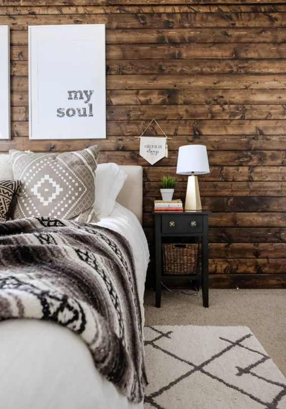 a farmhouse bedroom with a stained wooden wall, simple and cozy furniture, artworks and a table lamp and greenery