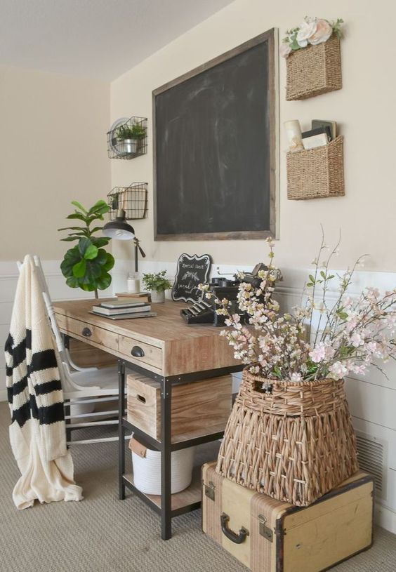 a farmhouse home office with a desk of wood and metal, baskets on the wall, a chalkboard and a cool white chair