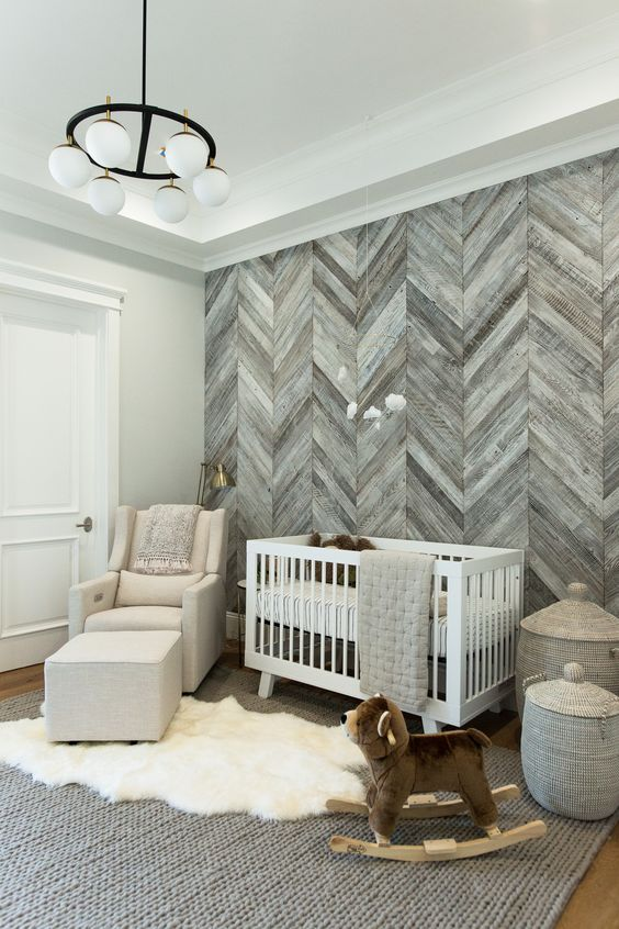 a farmhouse nursery with a grey wood herringbone wall, white furniture, a chic chandelier and layered rugs is very cozy