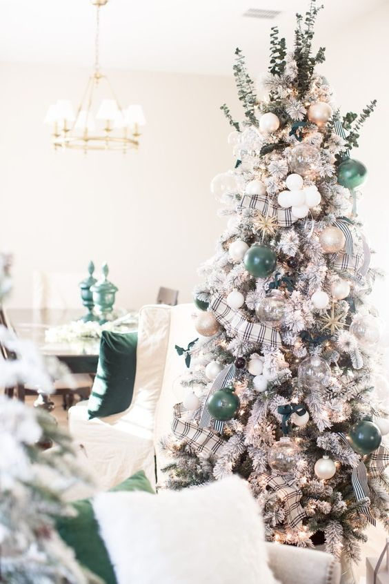a flocked Christmas tree with sheer, white, green and gold glitter ornaments, with plaid ribbons and fresh greenery on top