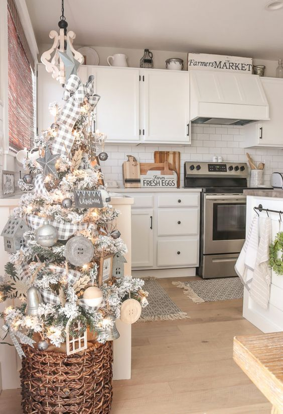 a flocked farmhouse Christmas tree with lights, buttons, bells, birdhouses and plaid ribbons in a basket is very lovely