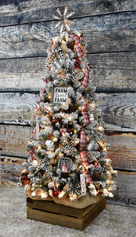 a flocked farmhouse Christmas tree with lights, plaid ribbons, a sign, a metal topper and some bells in various colors
