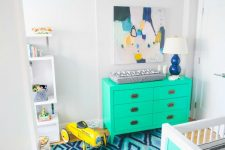 a fun and bright nursery with neon green furniture, a bright blue rug, a bold abstract artwork and a sunburst chandelier