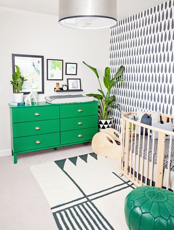 a fun nursery done in black and white, with lots of graphic patterns, a bold green dresser and an ottoman, statement plants and artworks