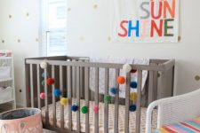 a fun nursery done with polka dot walls, a grey crib, white furniture, a pink rug, bright bedding, artworks and pompom garlands