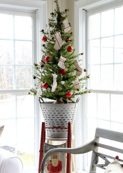 a fun tabletop Christmas tree decorated with red ornaments and striped stockings and put into a rustic bucket brings coziness