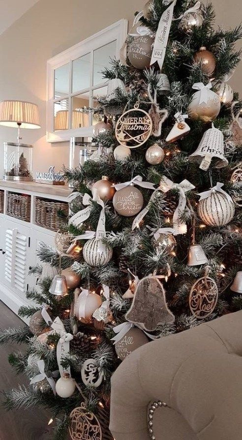 a glam rustic Christmas tree with taupe, grey and neutral ornaments, lights, bells, pinecones and bows and some carved wooden ornaments