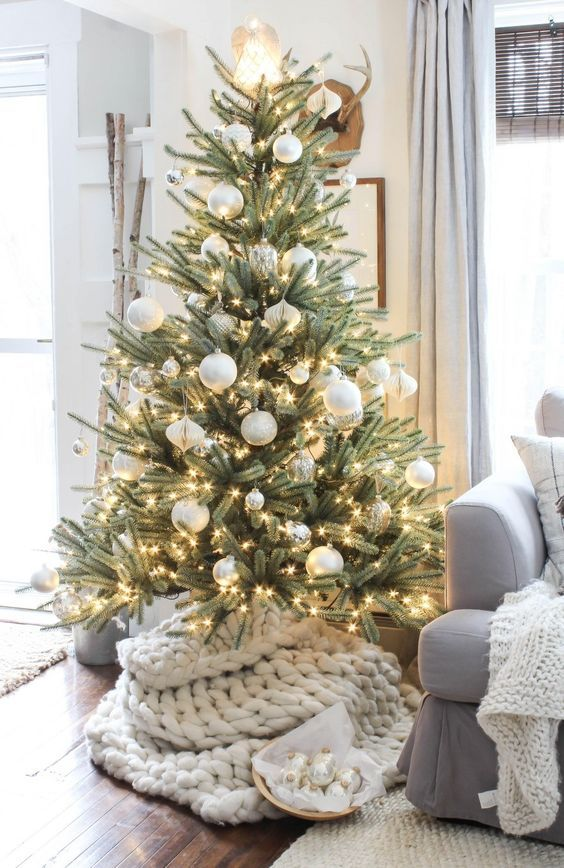 a gorgeoius and simple modern Christmas tree with white and silver ornaments of various sizes, lights and with a chunky knit cover