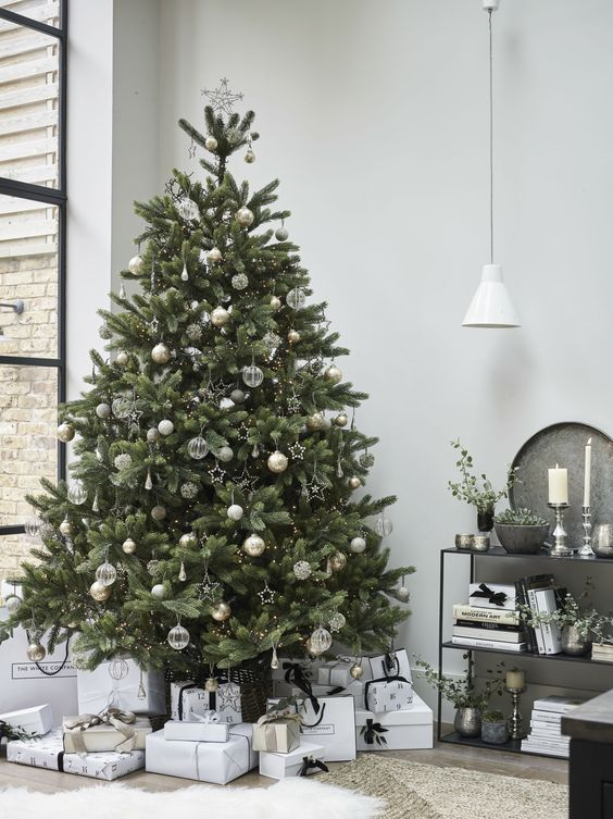 a gorgeous Christmas tree with sheer, white and gold ornaments, lights, star bead ornaments looks very laconic and very stylish