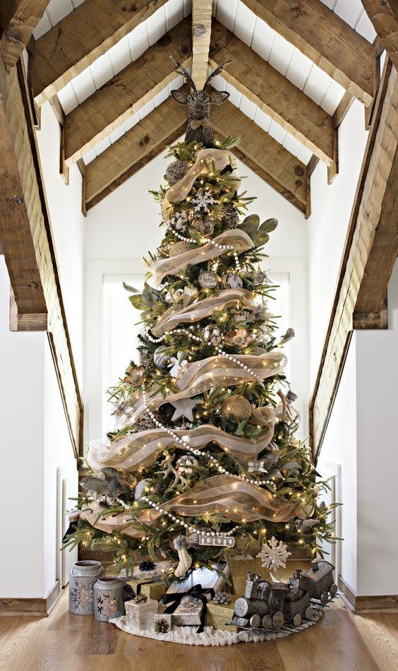 a gorgeous rustic Christmas tree with burlap ribbons, beaded garlands, lights, snowflakes, stockings and pale leaves plus a deer head