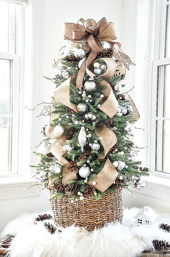 a gorgeous tabletop Christmas tree with silver and metallic ornaments, pinecones, twigs and a large burlap bow on top