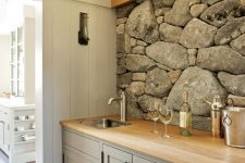 a home bar nook done with a stone accent wall, wooden beams and a grey cabinets that perfectly echo with the wall