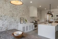 a kitchen and dining zone done in modern farmhouse style with a whitewashed stone accent wall that sets the tone and atmosphere here