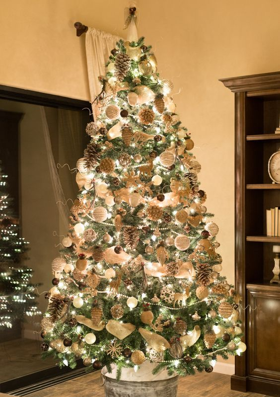 a luxurious rustic Christmas tree with lights, white and brown ornaments, snowy pinecones, deer, snowflakes and beads is wow