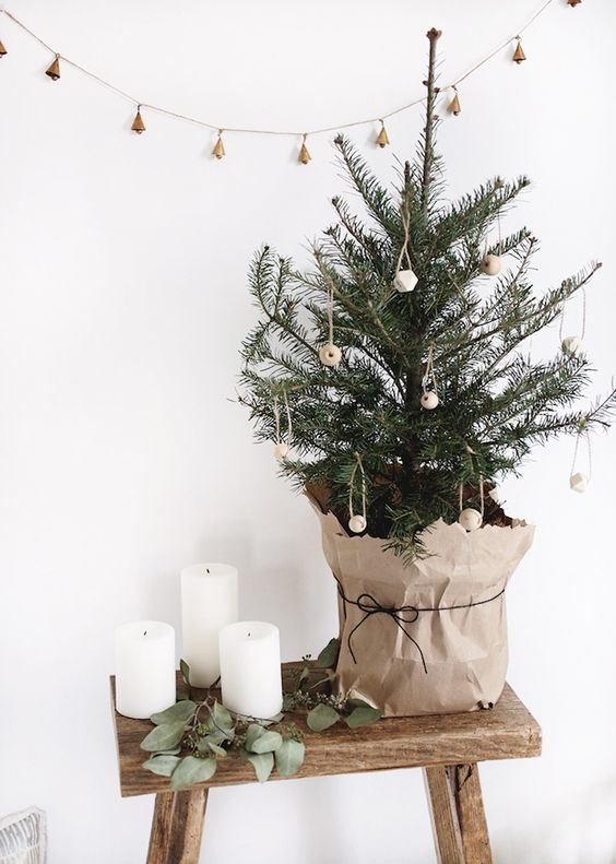 a minimalist Nordic tabletop Christmas tree decorated with wooden beads and wrapped into kraft paper is simple but cool