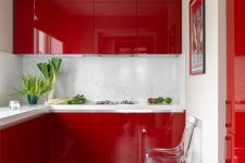 a minimalist deep red kitchen wotj a white stone backsplash and countertops and a sheer chair plus a bold artwork