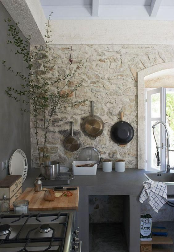 a minimalist meets industrial kitchen with graphite grey concrete walls and cabinets and a single stone accent wall for more coziness