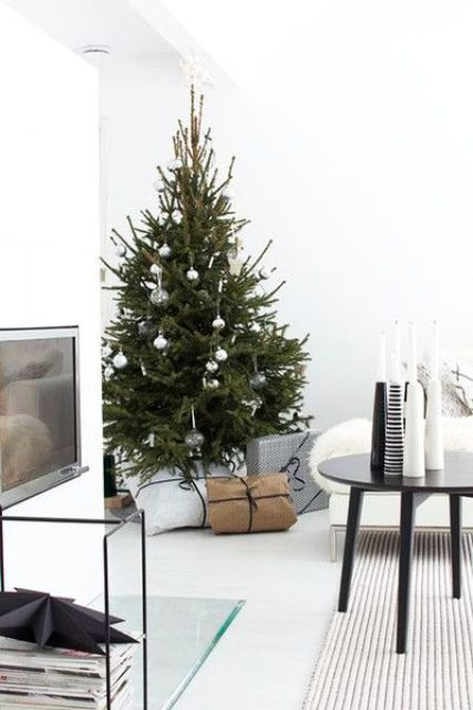 a modern Nordic Christmas tree decorated with silver, sheer and shiny metallic ornaments and some gifts under the tree