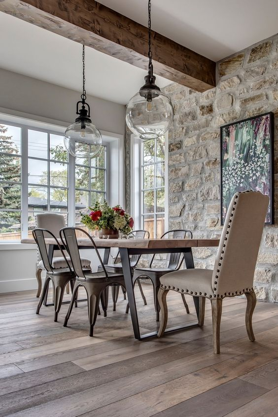 a modern French country kitchen with a stone accent wall, a wooden table and metal chairs and a leather chair plus pendant lamps