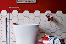 a modern and bold red and white bathroom with hex tiles, red walls and red grout, a tall sink standing and a hand holder