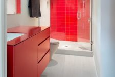 a modern bathroom with a red tile wall in the shower, a red sleek vanity and minimalist glass doors and a mirror