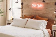 a modern bedroom with a whitewashed wooden wall, wooden furniture, sconces, statement plants and a pretty neon sign
